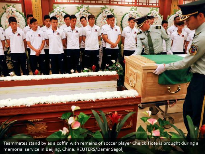 Teammates stand by as a coffin with remains of soccer player Cheick Tiote is brought during a memorial service in Beijing, China. REUTERS/Damir Sagolj
