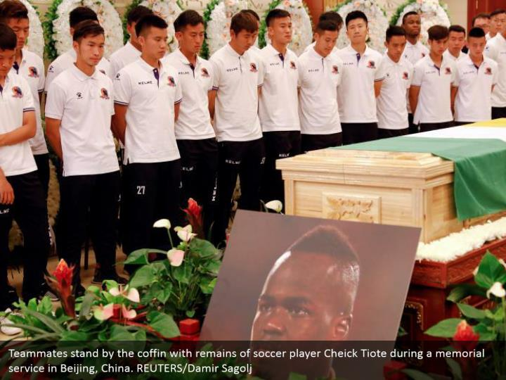 Teammates stand by the coffin with remains of soccer player Cheick Tiote during a memorial service in Beijing, China. REUTERS/Damir Sagolj