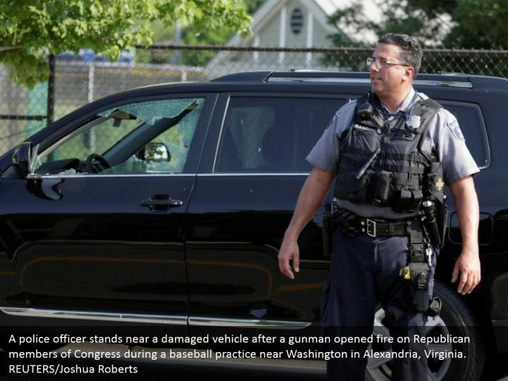 A police officer stands near a damaged vehicle after a gunman opened fire on Republican members of Congress during a baseball practice near Washington in Alexandria, Virginia. REUTERS/Joshua Roberts