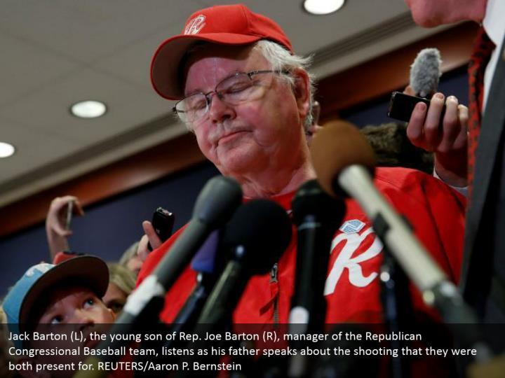Jack Barton (L), the young son of Rep. Joe Barton (R), manager of the Republican Congressional Baseball team, listens as his father speaks about the shooting that they were both present for. REUTERS/Aaron P. Bernstein