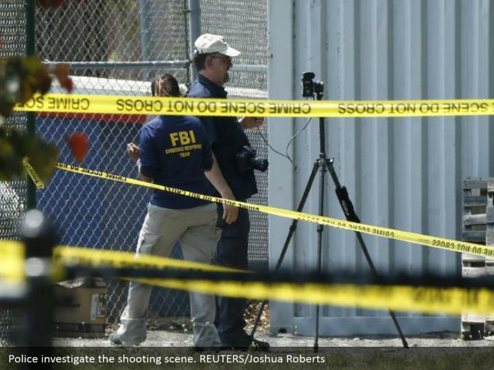 Police investigate the shooting scene. REUTERS/Joshua Roberts