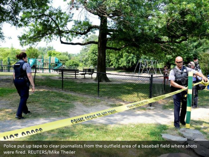 Police put up tape to clear journalists from the outfield area of a baseball field where shots were fired. REUTERS/Mike Theiler