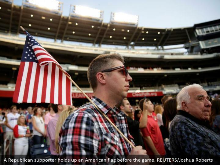 A Republican supporter holds up an American flag before the game. REUTERS/Joshua Roberts