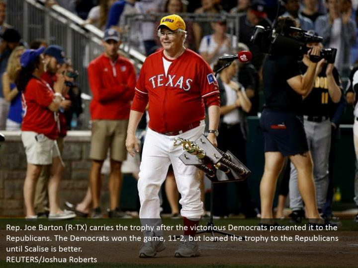 Rep. Joe Barton (R-TX) carries the trophy after the victorious Democrats presented it to the Republicans. The Democrats won the game, 11-2, but loaned the trophy to the Republicans until Scalise is better. REUTERS/Joshua Roberts