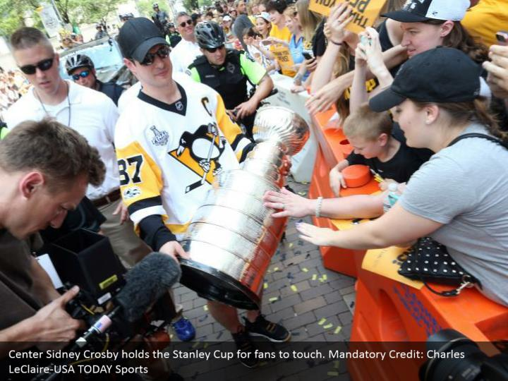 Center Sidney Crosby holds the Stanley Cup for fans to touch. Mandatory Credit: Charles LeClaire-USA TODAY Sports
