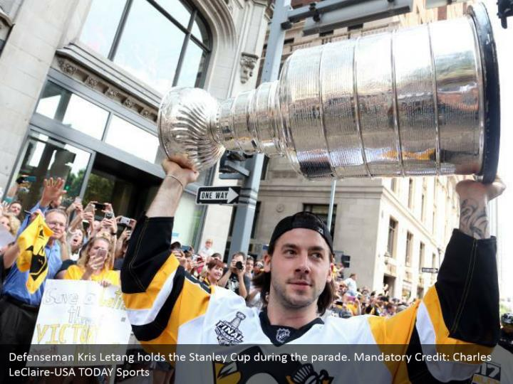 Defenseman Kris Letang holds the Stanley Cup during the parade. Mandatory Credit: Charles LeClaire-USA TODAY Sports