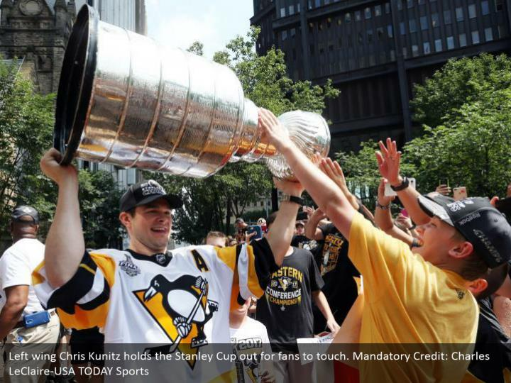 Left wing Chris Kunitz holds the Stanley Cup out for fans to touch. Mandatory Credit: Charles LeClaire-USA TODAY Sports