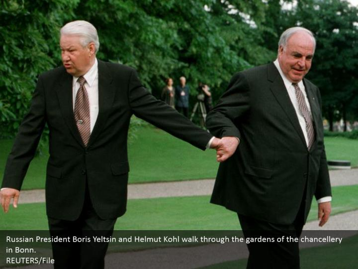 Russian President Boris Yeltsin and Helmut Kohl walk through the gardens of the chancellery in Bonn. REUTERS/File
