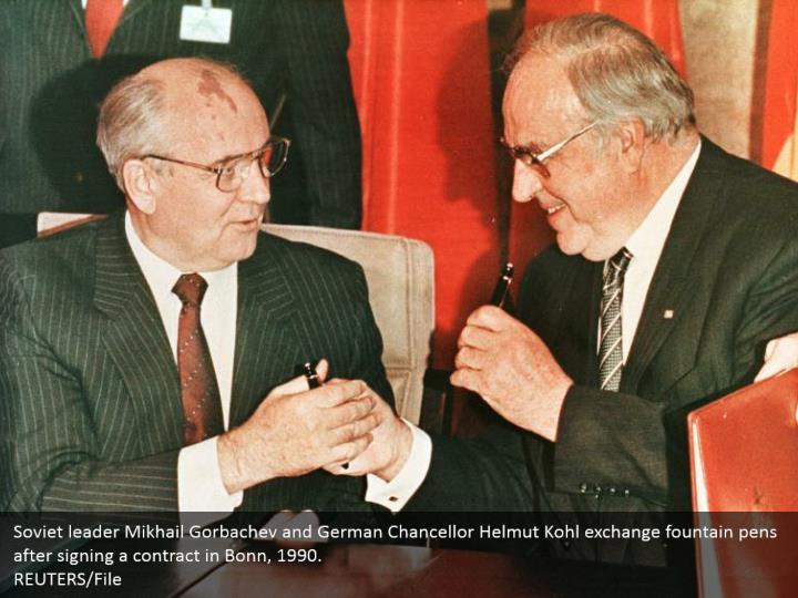 Soviet leader Mikhail Gorbachev and German Chancellor Helmut Kohl exchange fountain pens after signing a contract in Bonn, 1990. REUTERS/File