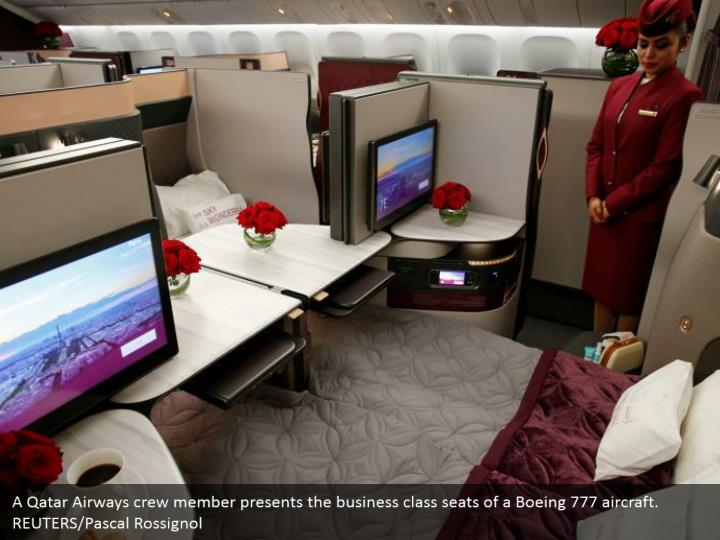 A Qatar Airways crew member presents the business class seats of a Boeing 777 aircraft. REUTERS/Pascal Rossignol