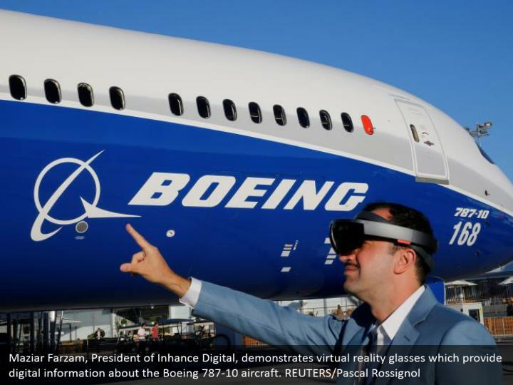 Maziar Farzam, President of Inhance Digital, demonstrates virtual reality glasses which provide digital information about the Boeing 787-10 aircraft. REUTERS/Pascal Rossignol