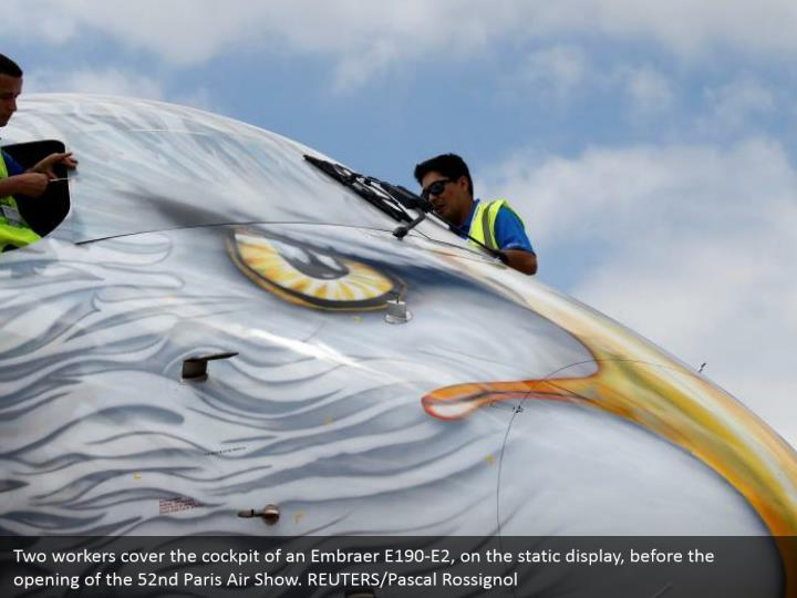 Two workers cover the cockpit of an Embraer E190-E2, on the static display, before the opening of the 52nd Paris Air Show. REUTERS/Pascal Rossignol