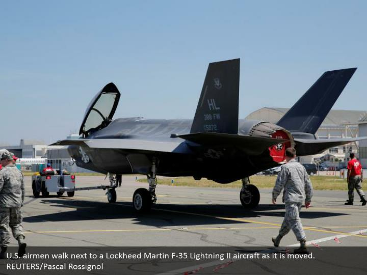 U.S. airmen walk next to a Lockheed Martin F-35 Lightning II aircraft as it is moved. REUTERS/Pascal Rossignol