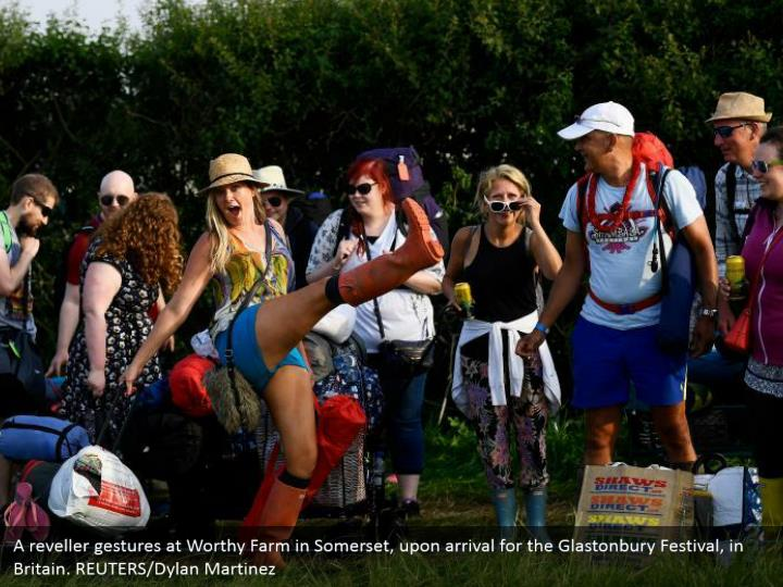 A reveller gestures at Worthy Farm in Somerset, upon arrival for the Glastonbury Festival, in Britain. REUTERS/Dylan Martinez