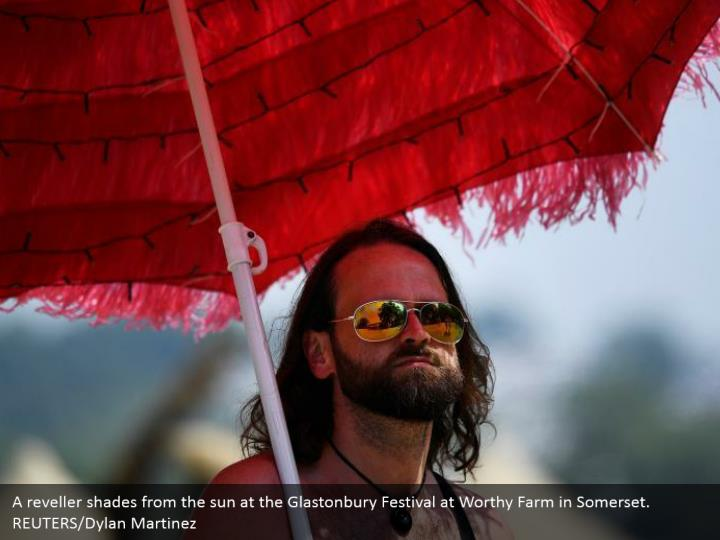 A reveller shades from the sun at the Glastonbury Festival at Worthy Farm in Somerset. REUTERS/Dylan Martinez