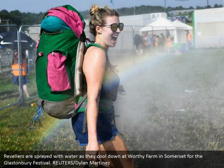 Revellers are sprayed with water as they cool down at Worthy Farm in Somerset for the Glastonbury Festival. REUTERS/Dylan Martinez
