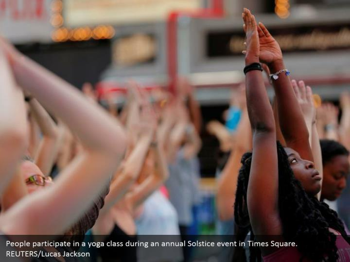 People participate in a yoga class during an annual Solstice event in Times Square. REUTERS/Lucas Jackson