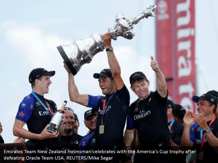 Emirates Team New Zealand Helmsman celebrates with the America's Cup trophy after defeating Oracle Team USA. REUTERS/Mike Segar