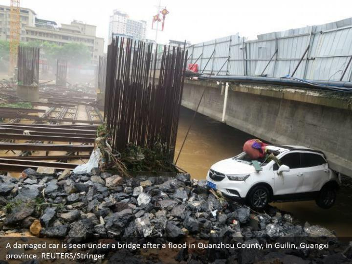 A damaged car is seen under a bridge after a flood in Quanzhou County, in Guilin, Guangxi province. REUTERS/Stringer