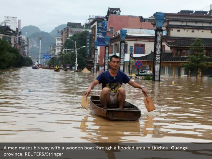 A man makes his way with a wooden boat through a flooded area in Liuzhou, Guangxi province. REUTERS/Stringer