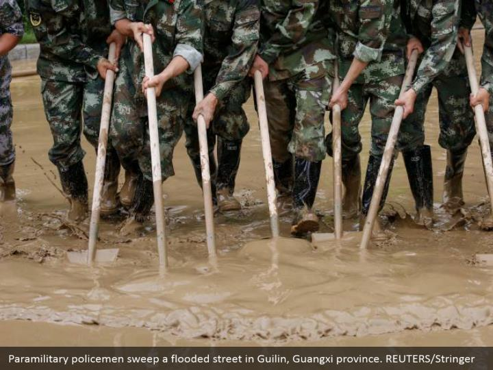 Paramilitary policemen sweep a flooded street in Guilin, Guangxi province. REUTERS/Stringer