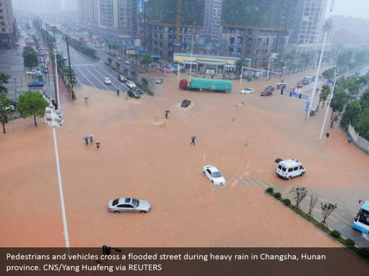 Pedestrians and vehicles cross a flooded street during heavy rain in Changsha, Hunan province. CNS/Yang Huafeng via REUTERS