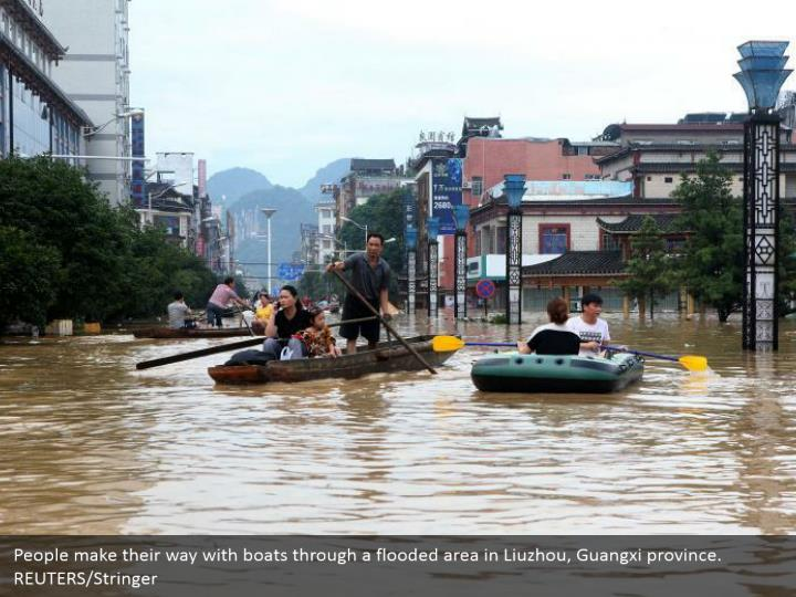 People make their way with boats through a flooded area in Liuzhou, Guangxi province. REUTERS/Stringer