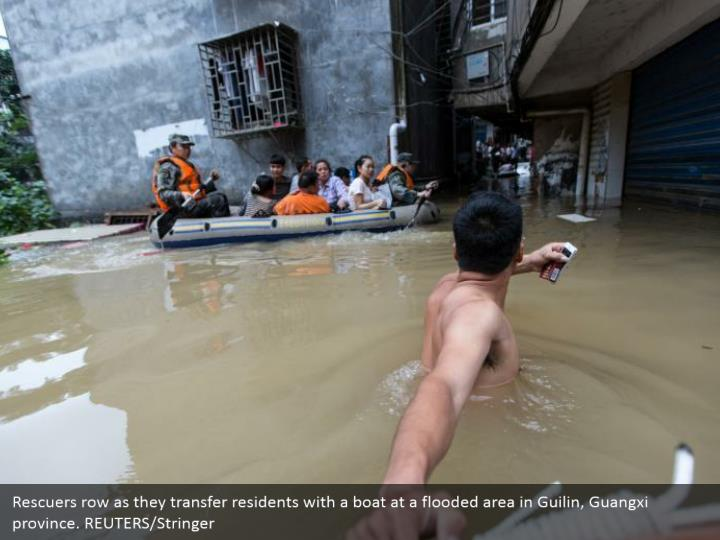 Rescuers row as they transfer residents with
