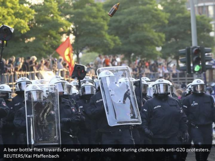 A beer bottle flies towards German riot police officers during clashes with anti-G20 protesters. REUTERS/Kai Pfaffenbach