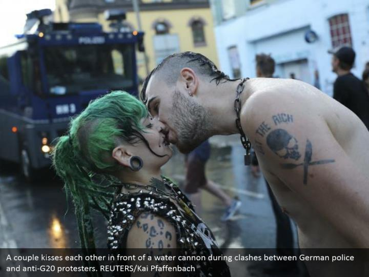 A couple kisses each other in front of a water cannon during clashes between German police and anti-G20 protesters. REUTERS/Kai Pfaffenbach