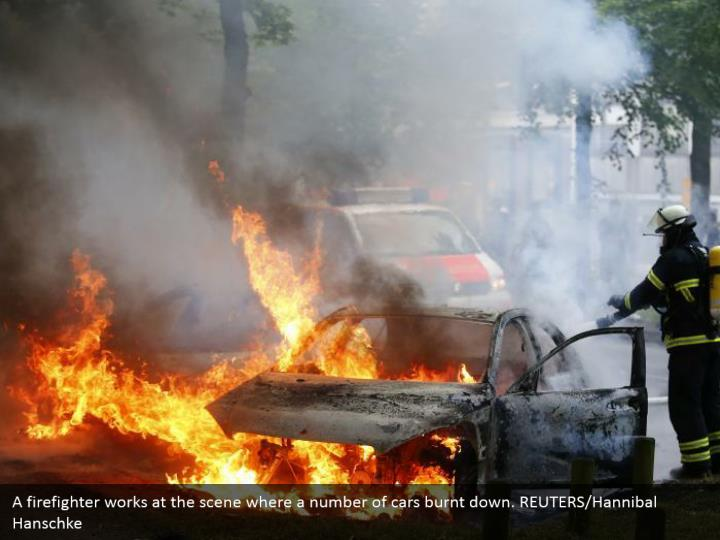 A firefighter works at the scene where a number of cars burnt down. REUTERS/Hannibal Hanschke