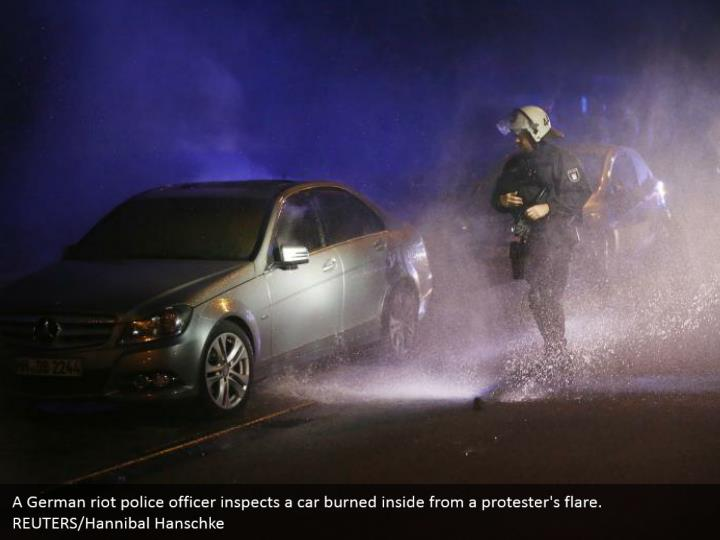 A German riot police officer inspects a car burned inside from a protester's flare. REUTERS/Hannibal Hanschke