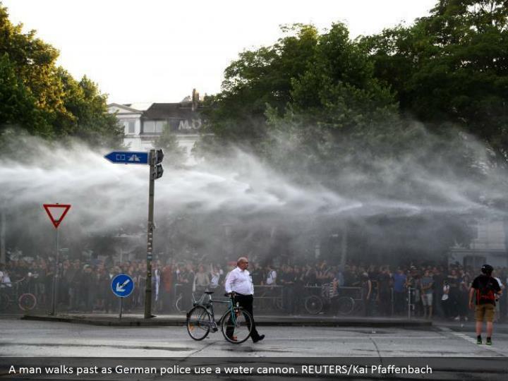 A man walks past as German police use a water cannon. REUTERS/Kai Pfaffenbach