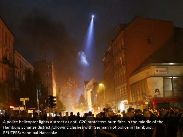A police helicopter lights a street as anti-G20 protesters burn fires in the middle of the Hamburg Schanze district following clashes with German riot police in Hamburg. REUTERS/Hannibal Hanschke