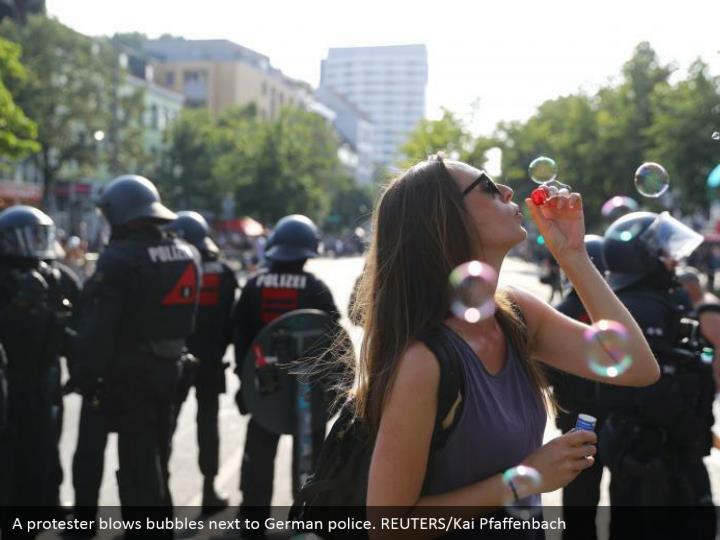A protester blows bubbles next to German police. REUTERS/Kai Pfaffenbach