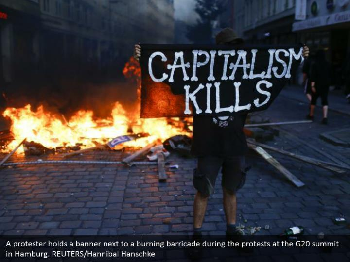 A protester holds a banner next to a burning barricade during the protests at the G20 summit in Hamburg. REUTERS/Hannibal Hanschke