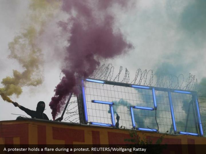 A protester holds a flare during a protest. REUTERS/Wolfgang Rattay