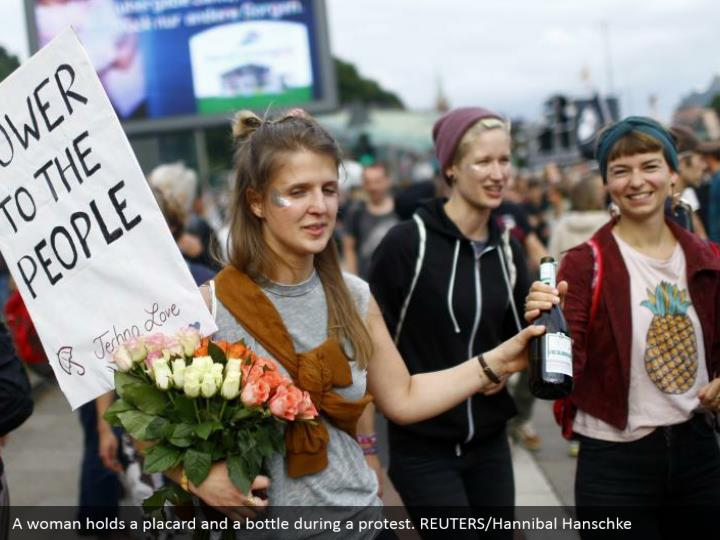 A woman holds a placard and a bottle during a protest. REUTERS/Hannibal Hanschke