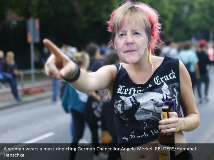 A woman wears a mask depicting German Chancellor Angela Merkel. REUTERS/Hannibal Hanschke