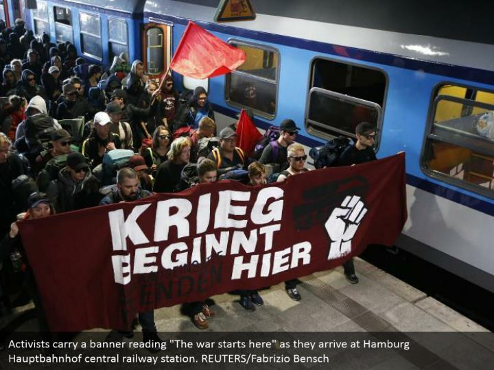 """Activists carry a banner reading """"The war starts here"""" as they arrive at Hamburg Hauptbahnhof central railway station. REUTERS/Fabrizio Bensch"""
