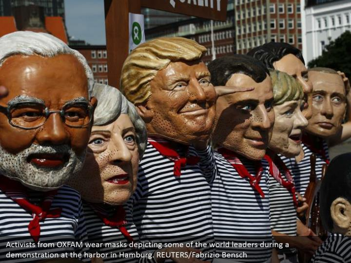 Activists from OXFAM wear masks depicting some of the world leaders during a demonstration at the harbor in Hamburg. REUTERS/Fabrizio Bensch