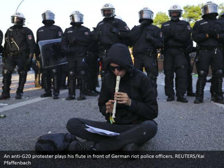 An anti-G20 protester plays his flute in front of German riot police officers. REUTERS/Kai Pfaffenbach
