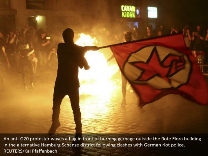 An anti-G20 protester waves a flag in front of burning garbage outside the Rote Flora building in the alternative Hamburg Schanze district following clashes with German riot police. REUTERS/Kai Pfaffenbach