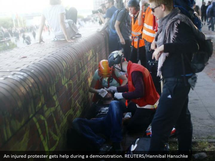 An injured protester gets help during a demonstration. REUTERS/Hannibal Hanschke