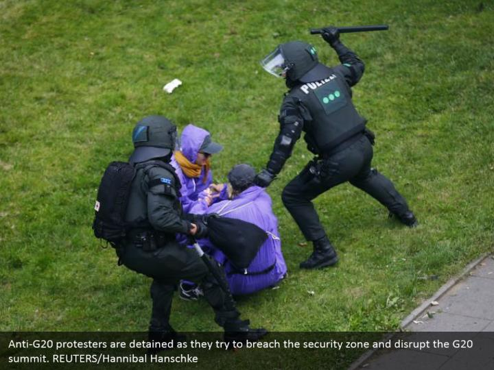 Anti-G20 protesters are detained as they try to breach the security zone and disrupt the G20 summit. REUTERS/Hannibal Hanschke