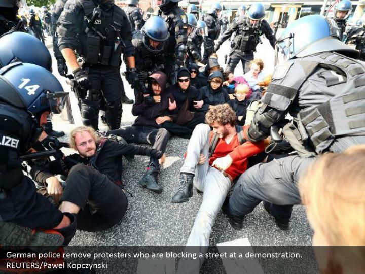 German police remove protesters who are blocking a street at a demonstration. REUTERS/Pawel Kopczynski