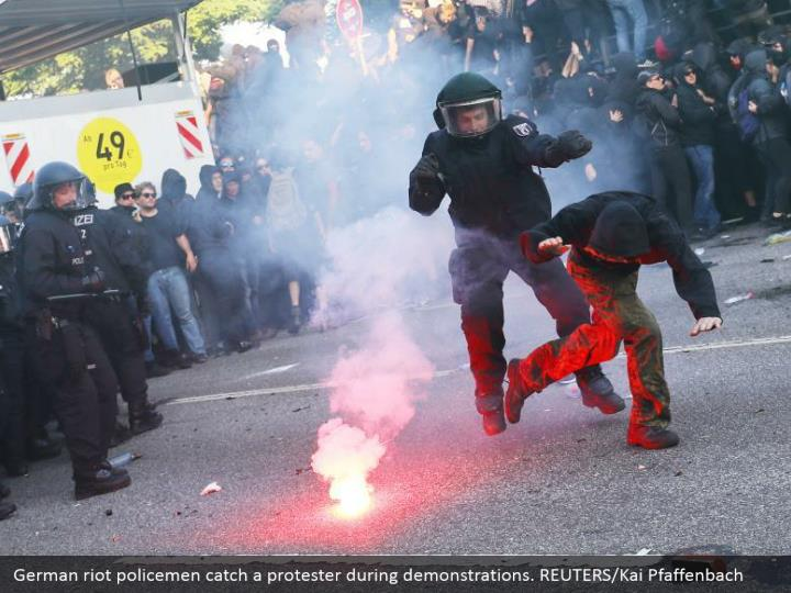 German riot policemen catch a protester during demonstrations. REUTERS/Kai Pfaffenbach
