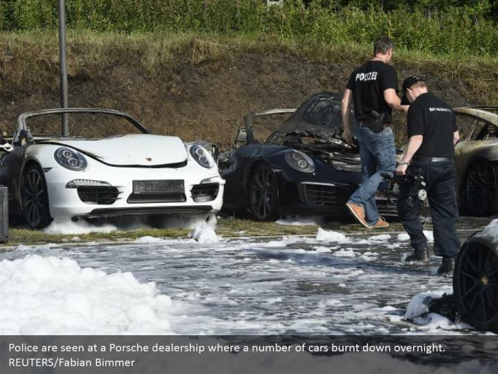 Police are seen at a Porsche dealership where a number of cars burnt down overnight. REUTERS/Fabian Bimmer