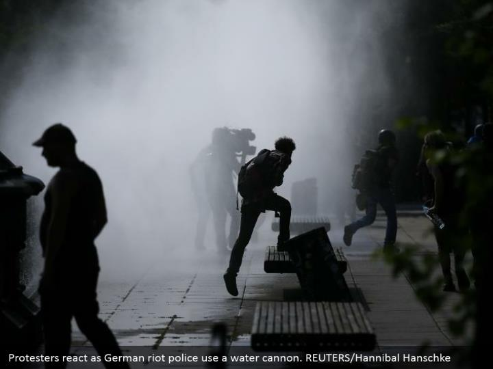 Protesters react as German riot police use a water cannon. REUTERS/Hannibal Hanschke