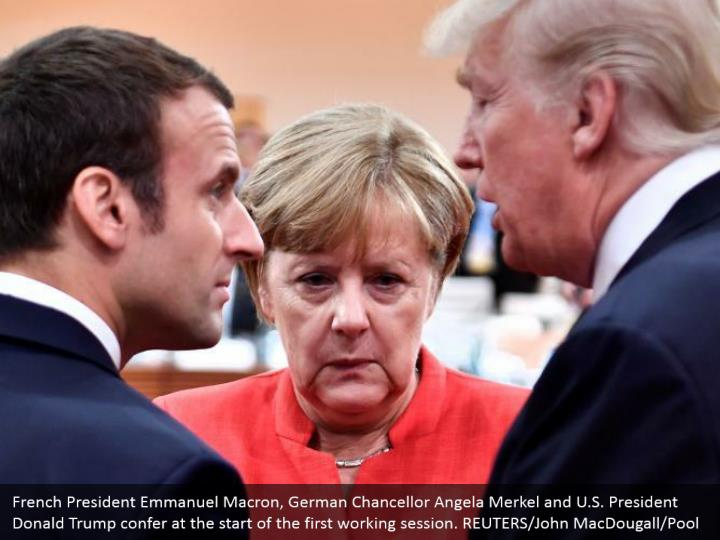 French President Emmanuel Macron, German Chancellor Angela Merkel and U.S. President Donald Trump confer at the start of the first working session. REUTERS/John MacDougall/Pool